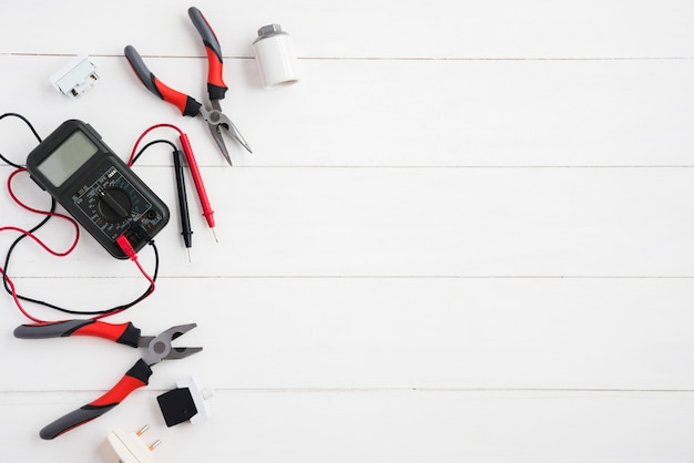 Vista elevata del multimetro digitale e delle attrezzature elettriche sullo scrittorio di legno bianco
