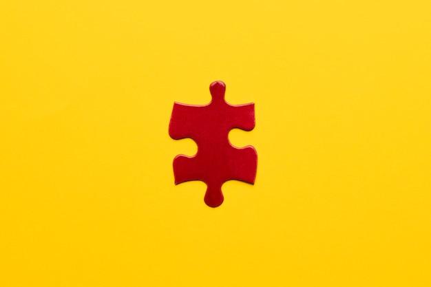 Vista elevata del pezzo di puzzle rosso su sfondo giallo
