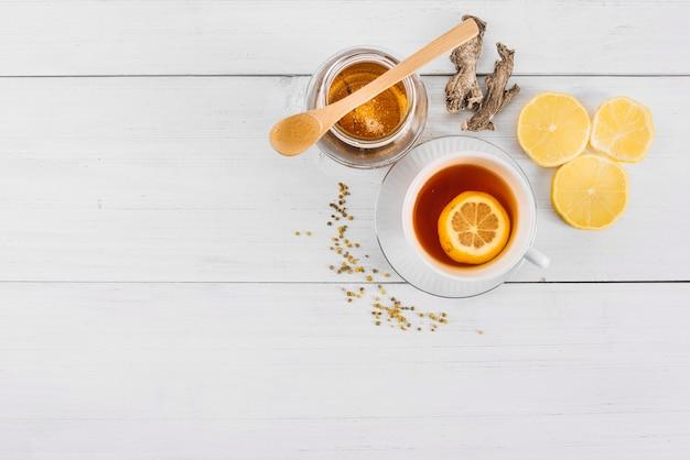 Vista elevata del tè al limone; miele e zenzero sullo sfondo in legno