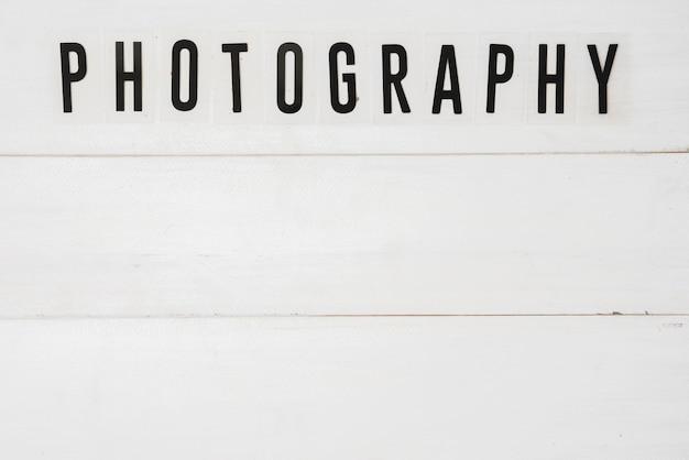 Vista elevata del testo di fotografia sopra la tavola di legno bianca