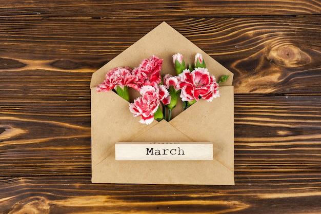 Vista elevata del testo di marzo sul blocco di legno sopra la busta con i fiori rossi