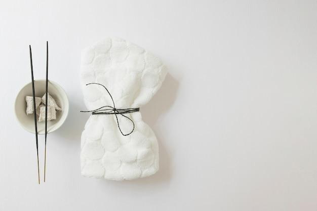 Vista elevata del tovagliolo legato; bastoncino di incenso e pietra pomice su superficie bianca