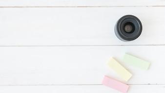 Vista elevata dell'obiettivo moderno con note adesive colorate sul tavolo di legno