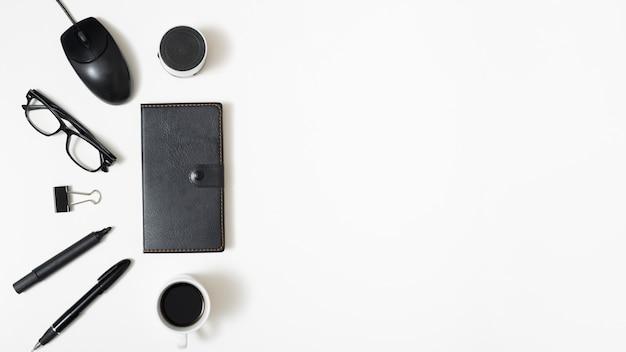 Vista elevata dell'altoparlante bluetooth; topo; occhiali da vista; graffetta per fogli; penna e tazza di caffè con diario su sfondo bianco