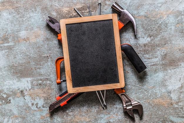 Vista elevata dell'ardesia vuota su vari strumenti di lavoro