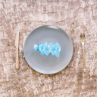 Vista elevata della bottiglia di plastica sgualcita sul piatto tra forchetta e coltello da cucina