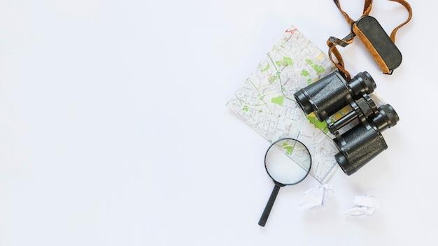 Vista elevata della carta velina accartocciata; carta geografica; binocolo e lente d'ingrandimento su sfondo bianco