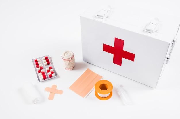 Vista elevata della cassetta di pronto soccorso con le attrezzature mediche su fondo bianco