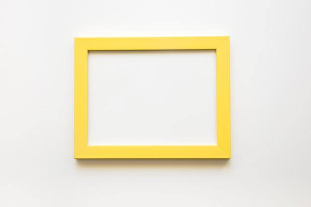 Vista elevata della cornice gialla vuota su sfondo bianco