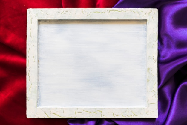 Vista elevata della cornice in bianco su tessuto rosso e viola