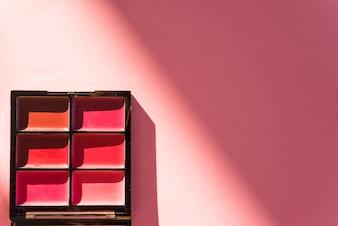 Vista elevata della gamma di colori cosmetici ombretto su sfondo rosso
