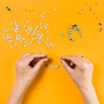 Vista elevata della mano che fa il braccialetto dalla perla della lettera