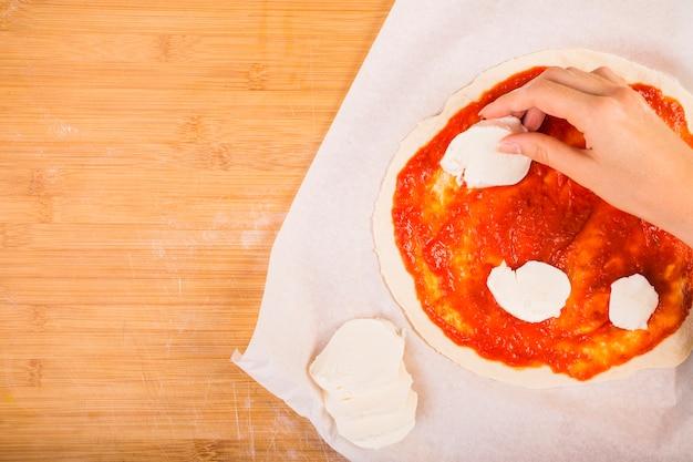 Vista elevata della mano di una donna che mette formaggio sulla pasta