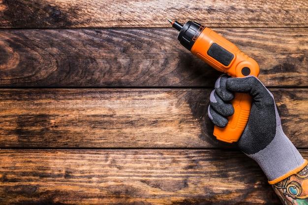 Vista elevata della mano di una persona che tiene trapano cordless su fondo di legno