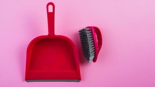 Vista elevata della paletta per la spazzatura rossa e pennello su sfondo rosa