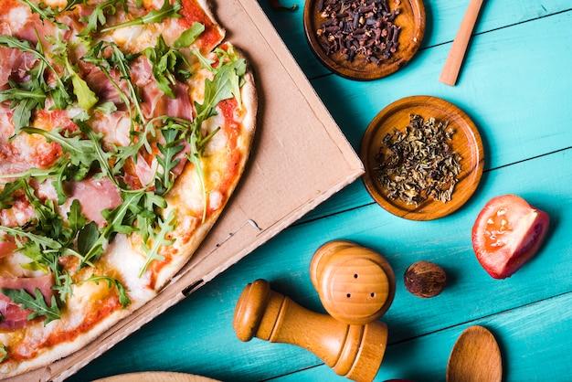 Vista elevata della pizza al bacon italiana alle erbe; fetta di pomodoro; chiodi di garofano e peppermill su sfondo di colore turchese