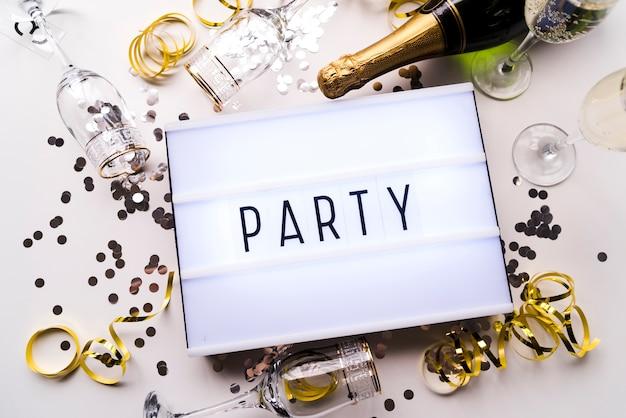 Vista elevata della scatola leggera e del champagne del testo del partito con i coriandoli su fondo bianco