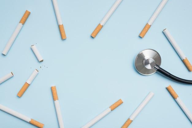 Vista elevata della sigaretta e dello stetoscopio su priorità bassa blu