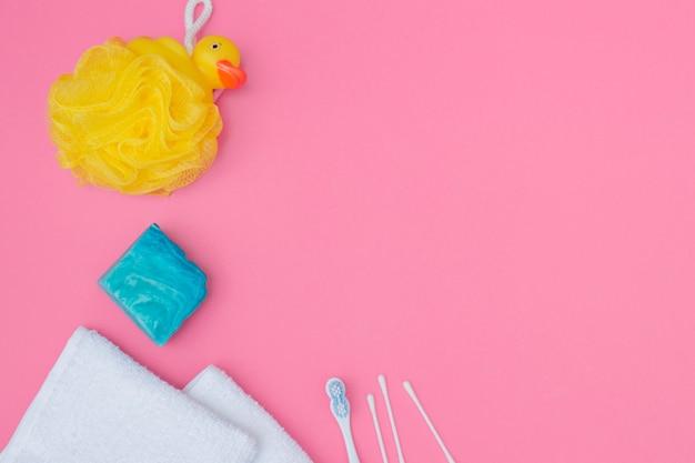 Vista elevata della spugna da bagno; sapone; tampone di cotone e asciugamano su sfondo rosa