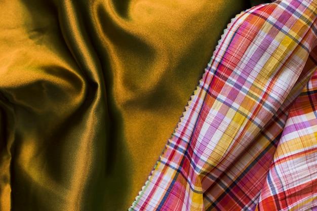 Vista elevata della tovaglia a scacchi modello su tessile dorato serico