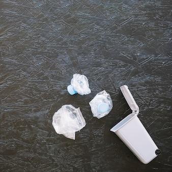 Vista elevata delle bottiglie di acqua di plastica sgualcite vicino alla pattumiera miniatura