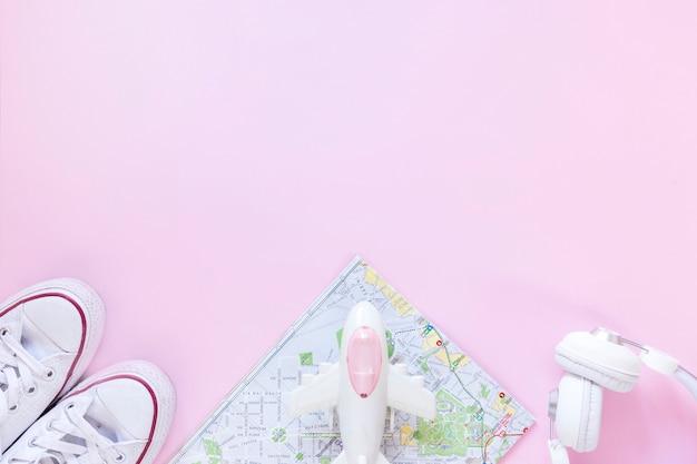 Vista elevata delle calzature; carta geografica; aereo e auricolare su sfondo rosa