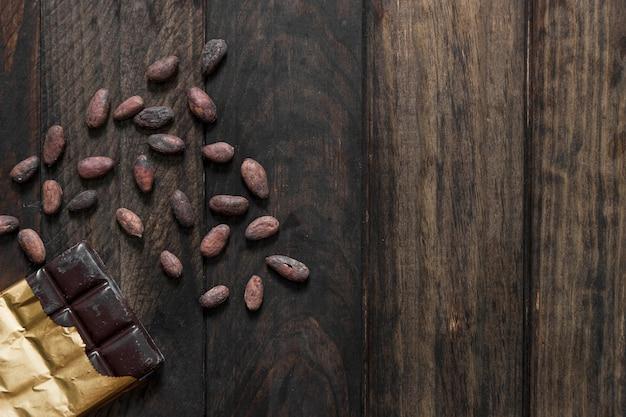 Vista elevata delle fave di cacao e della barra di cioccolato arrostite sulla tavola di legno