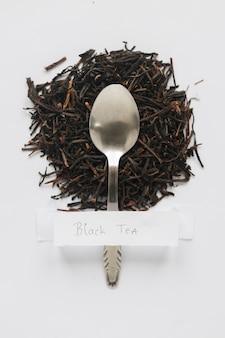Vista elevata delle foglie di tè nere asciutte con l'etichetta bianca sul contesto bianco