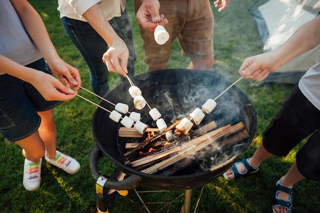 Vista elevata delle mani che arrostiscono caramella gommosa e molle sul fuoco del barbecue
