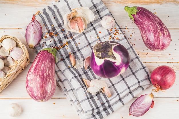 Vista elevata delle melanzane; cipolla; spicchi d'aglio e stoffa motivo a scacchi sulla tavola di legno