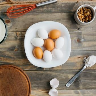 Vista elevata delle uova; farina e noce con frusta su fondo in legno