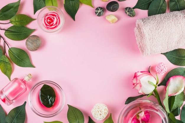 Vista elevata di asciugamani; pietre spa; olio fiore e foglie che formano una cornice sulla superficie rosa