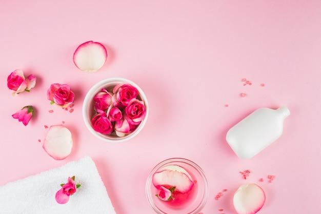 Vista elevata di asciugamano; fiori e bottiglia su sfondo rosa