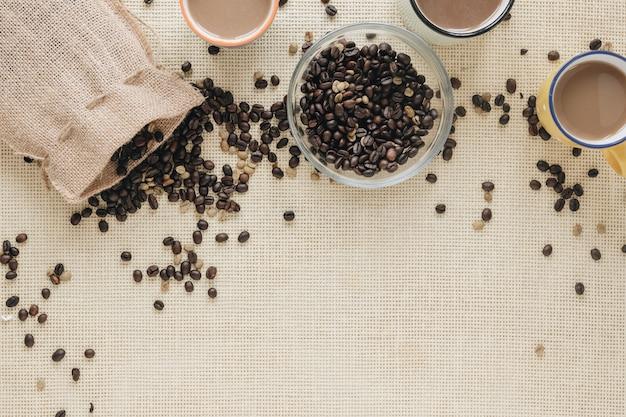 Vista elevata di caffè fresco in tazza con chicchi di caffè
