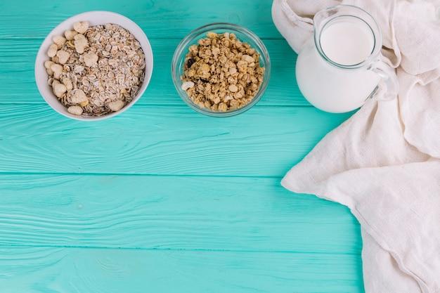 Vista elevata di ciotole di cereali; barattolo di latte sulla tavola di legno verde
