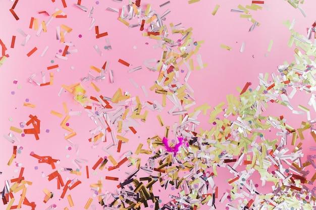 Vista elevata di coriandoli colorati su sfondo rosa