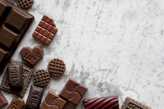Vista elevata di deliziose barrette di cioccolato su sfondo bianco strutturato