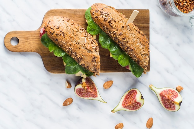 Vista elevata di deliziosi hot dog sul tagliere di legno vicino alle fette di fico; mandorle e barattolo di peperoncino si scaglia su marmo bianco
