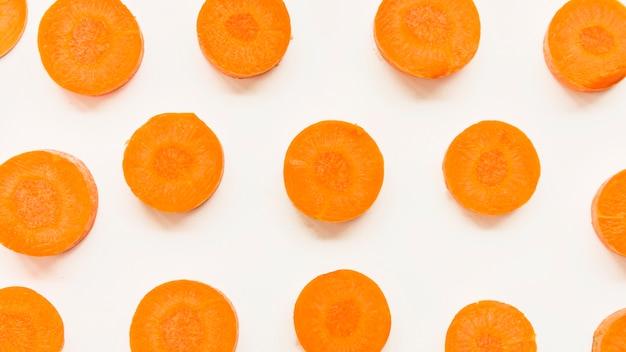 Vista elevata di fette di carota su sfondo bianco