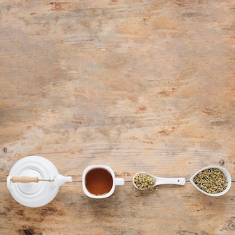 Vista elevata di fiori secchi di crisantemo cinese; teiera e tè al limone disposti in fila sul tavolo