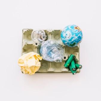 Vista elevata di globo, lampadina, carta accartocciata, bottiglia di plastica e batterie sul cartone delle uova