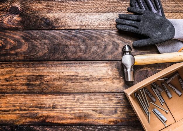 Vista elevata di guanti, martello, chiodi e tasselli su fondo in legno