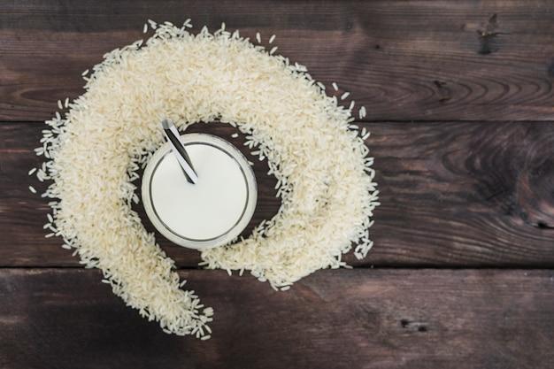 Vista elevata di latte di riso e chicchi di riso disposti su fondo stagionato
