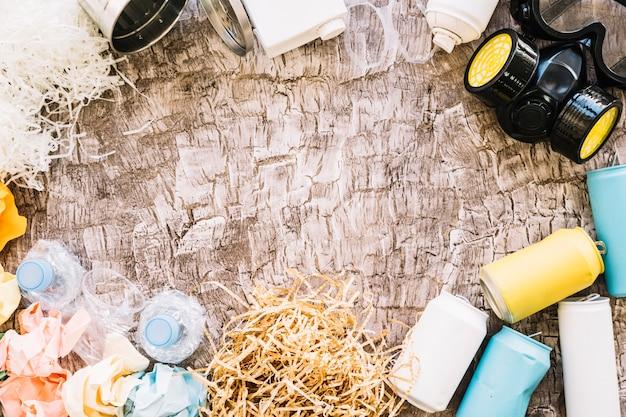 Vista elevata di maschera antigas, lattine, carta stropicciata e bottiglie di plastica sul fondale in legno