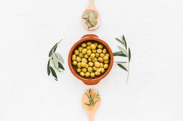 Vista elevata di olio d'oliva con rosmarino su priorità bassa bianca