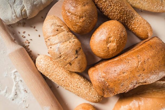 Vista elevata di pane con varie forme e mattarello