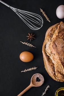 Vista elevata di pane delizioso con ingredienti di cottura e utensili su sfondo nero