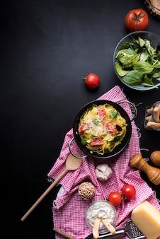 Vista elevata di pasta fresca fettuccine in contenitore con verdure a foglia e ingredienti sulla superficie nera