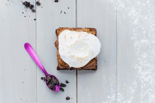 Vista elevata di pasticceria fresca con cioccolato sul cucchiaio sopra la plancia di legno