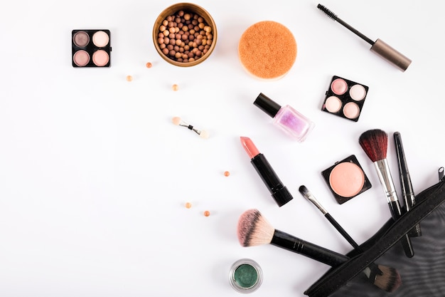 Vista elevata di pennelli trucco e cosmetici su sfondo bianco